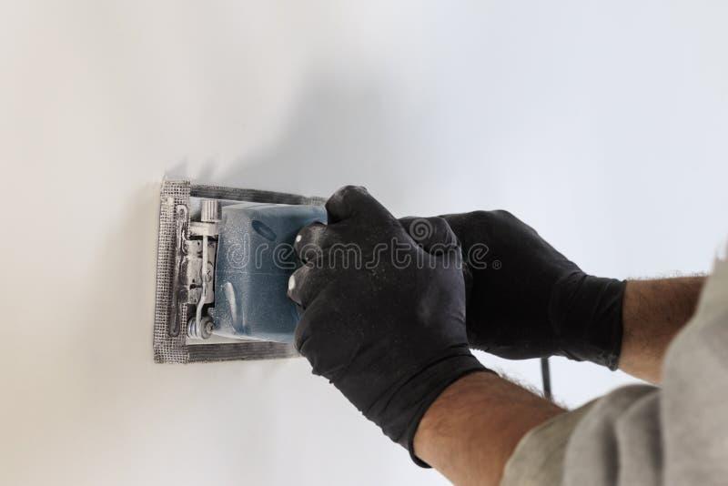 Εργασία λήξης - ο κύριος ευθυγραμμίζει τον τοίχο με sander, έχει τη σκόνη στην οποία λειτουργεί υπάρχει tanirovanie στοκ φωτογραφία με δικαίωμα ελεύθερης χρήσης