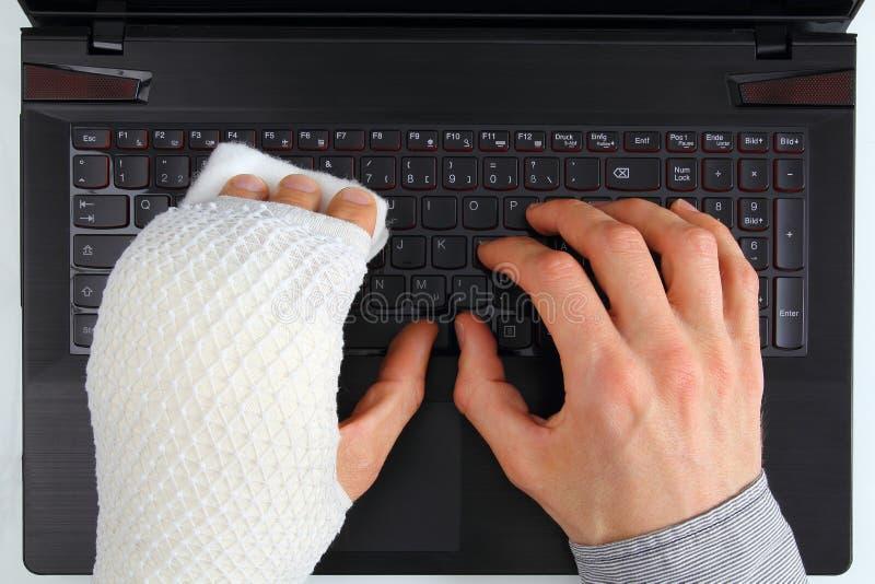 Εργασία σε ένα σημειωματάριο με τον τραυματισμό χεριών στοκ εικόνα με δικαίωμα ελεύθερης χρήσης