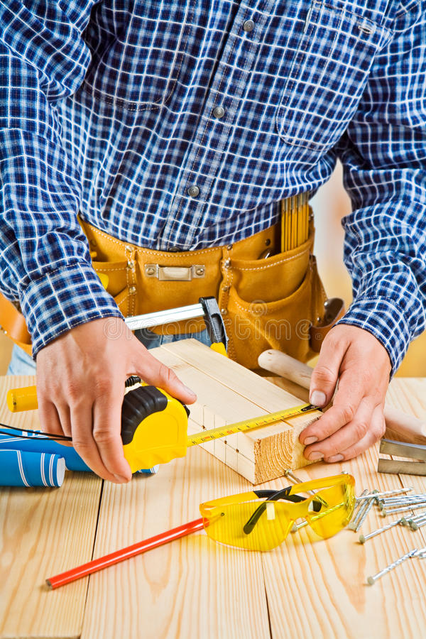 Εργασία του ξυλουργού. μέτρηση με τη ρουλέτα στοκ φωτογραφίες