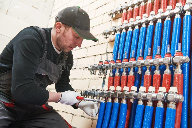 Εργασία υδραυλικών Εγκατάσταση του συλλέκτη για το θερμό σύστημα underfloor θέρμανσης νερού στοκ φωτογραφίες