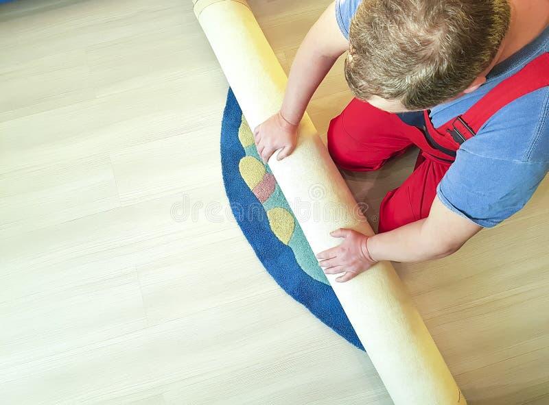 Εργασία χεριών, που διπλώνει τον τάπητα εργασίας στο πάτωμα του σπιτιού στοκ εικόνες με δικαίωμα ελεύθερης χρήσης