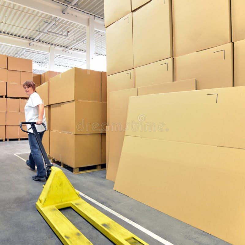 Εργασίες γυναικών με forklift το φορτηγό σε μια αποθήκη εμπορευμάτων με τα χαρτοκιβώτια στοκ εικόνες με δικαίωμα ελεύθερης χρήσης