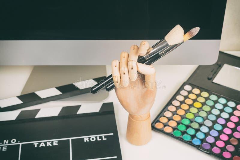 Εργασιακός χώρος καλλιτεχνών Makeup με την παλέτα makeup με τις βούρτσες, πληκτρολόγιο, όργανο ελέγχου υπολογιστών, clapboard στοκ φωτογραφία με δικαίωμα ελεύθερης χρήσης