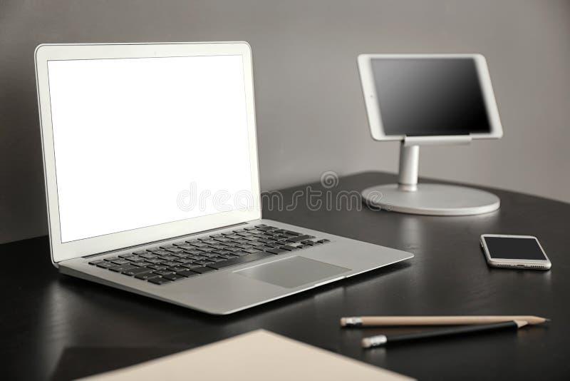 Εργασιακός χώρος με τις σύγχρονες συσκευές στον πίνακα στην αρχή στοκ εικόνα με δικαίωμα ελεύθερης χρήσης