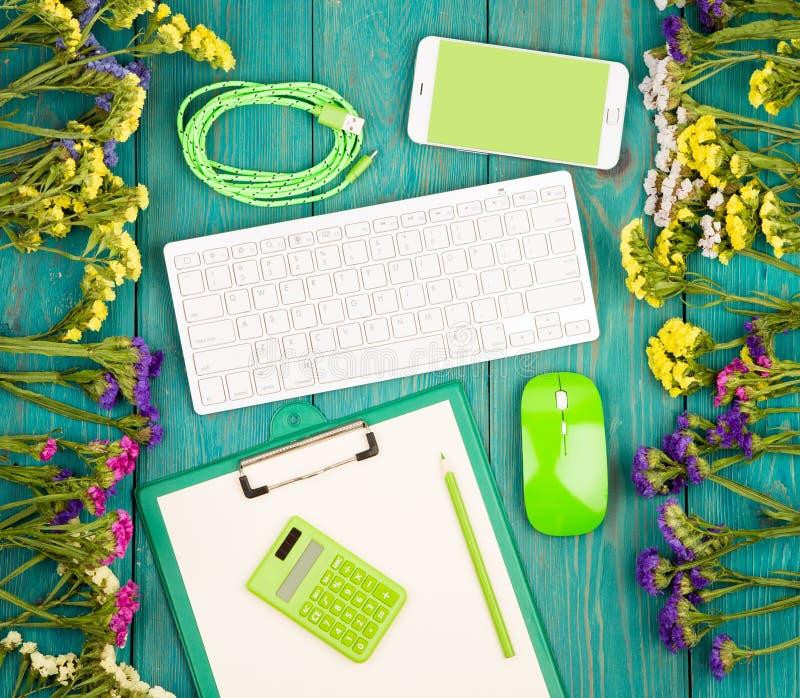 Εργασιακός χώρος με το ασύρματο λεπτό πληκτρολόγιο, πράσινο ποντίκι, έξυπνο τηλέφωνο, στοκ φωτογραφία