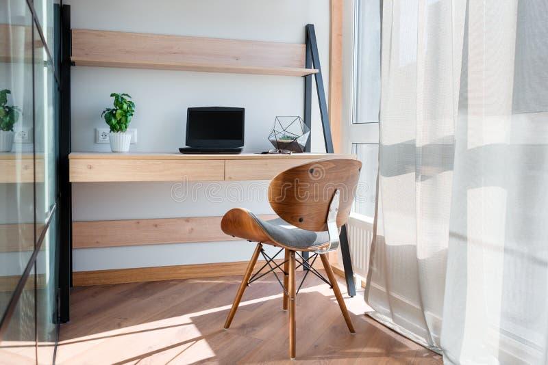Εργασιακός χώρος με το lap-top στον πίνακα Άνετος πίνακας εργασίας στο γραφείο κοντά στο παράθυρο Σχέδιο του εργασιακού χώρου στο στοκ φωτογραφία με δικαίωμα ελεύθερης χρήσης