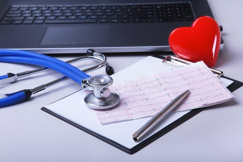 Εργασιακός χώρος του γιατρού με το lap-top, το στηθοσκόπιο, τη συνταγή RX, τα γυαλιά και την κόκκινα καρδιά και το σημειωματάριο  στοκ φωτογραφία