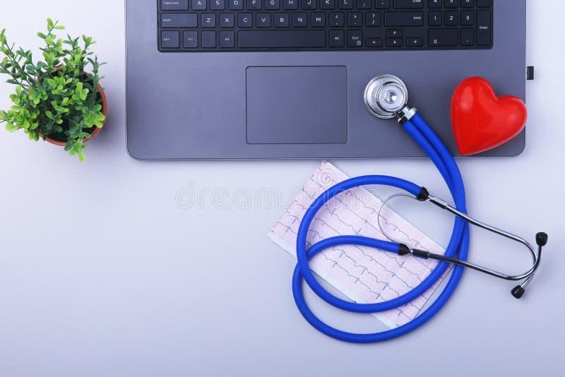 Εργασιακός χώρος του γιατρού με το lap-top, το στηθοσκόπιο, τη συνταγή RX, τα γυαλιά και την κόκκινα καρδιά και το σημειωματάριο  στοκ φωτογραφία με δικαίωμα ελεύθερης χρήσης