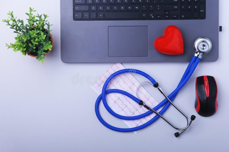 Εργασιακός χώρος του γιατρού με το lap-top, το στηθοσκόπιο, τη συνταγή RX, τα γυαλιά και την κόκκινα καρδιά και το σημειωματάριο  στοκ εικόνα