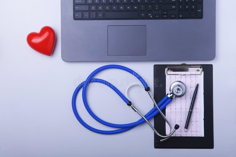 Εργασιακός χώρος του γιατρού με το lap-top, το στηθοσκόπιο, τη συνταγή RX, τα γυαλιά και την κόκκινα καρδιά και το σημειωματάριο  στοκ εικόνες