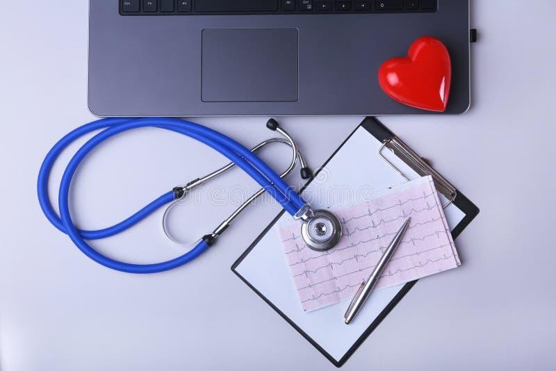 Εργασιακός χώρος του γιατρού με το lap-top, το στηθοσκόπιο, τη συνταγή RX, τα γυαλιά και την κόκκινα καρδιά και το σημειωματάριο  στοκ φωτογραφίες με δικαίωμα ελεύθερης χρήσης