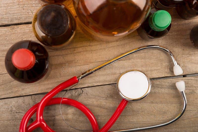 Εργασιακός χώρος του γιατρού - μπουκάλια στηθοσκοπίων και φαρμακείων στο ξύλινο γραφείο στοκ εικόνα