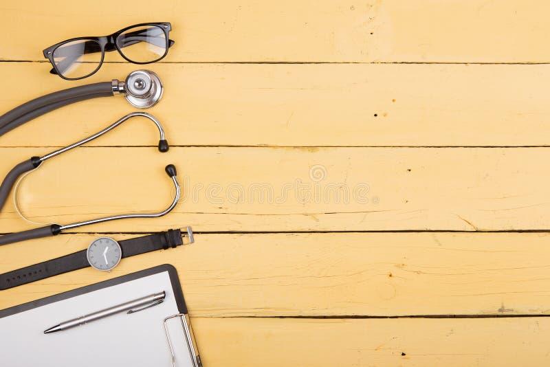 Εργασιακός χώρος του γιατρού - στηθοσκόπιο και άλλες προμήθειες στο κίτρινο ξύλινο γραφείο στοκ εικόνα με δικαίωμα ελεύθερης χρήσης