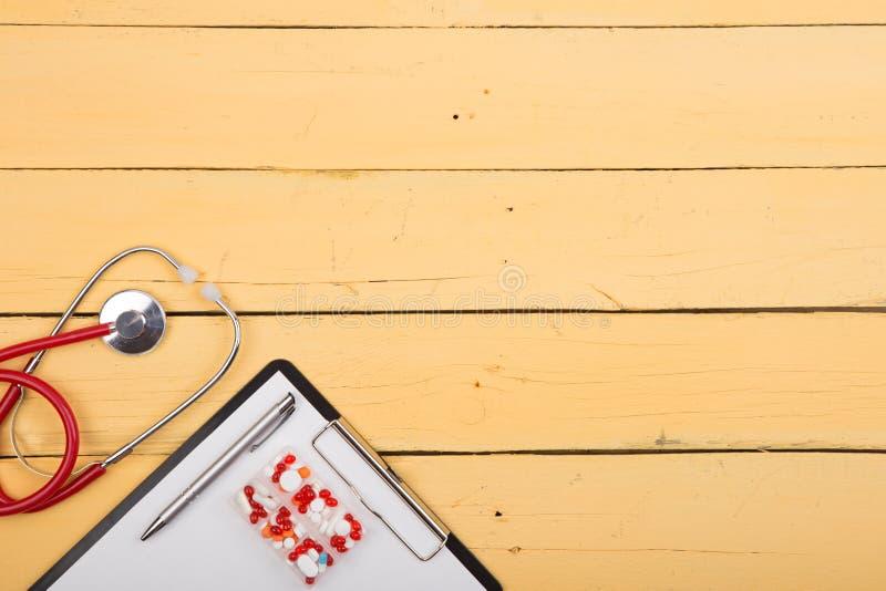Εργασιακός χώρος του γιατρού - στηθοσκόπιο και άλλες προμήθειες στο κίτρινο ξύλινο γραφείο στοκ φωτογραφίες
