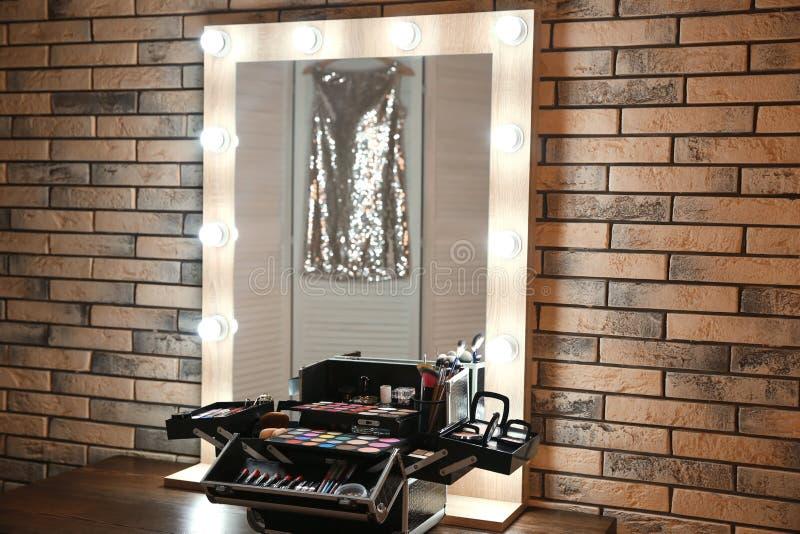 Εργασιακός χώρος του επαγγελματικού καλλιτέχνη makeup με τον καθρέφτη και το καλλυντικό στοκ φωτογραφίες