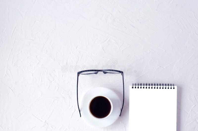 Εργασιακός χώρος Fletley με ένα σημειωματάριο, έναν καφέ και τα γυαλιά στοκ φωτογραφίες