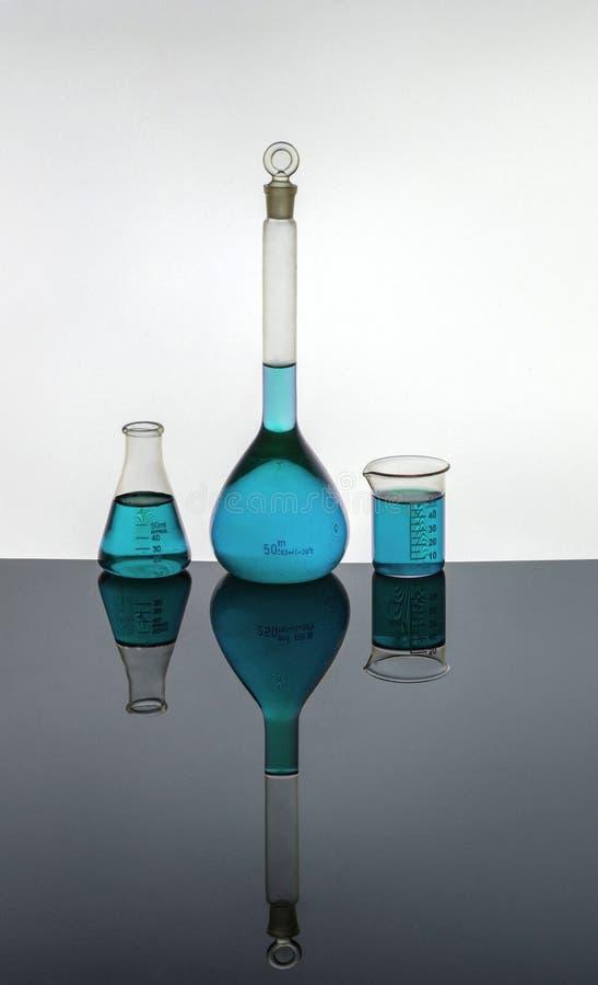 Εργαστηριακά γυαλικά που περιέχουν τις μπλε λύσεις στοκ εικόνα