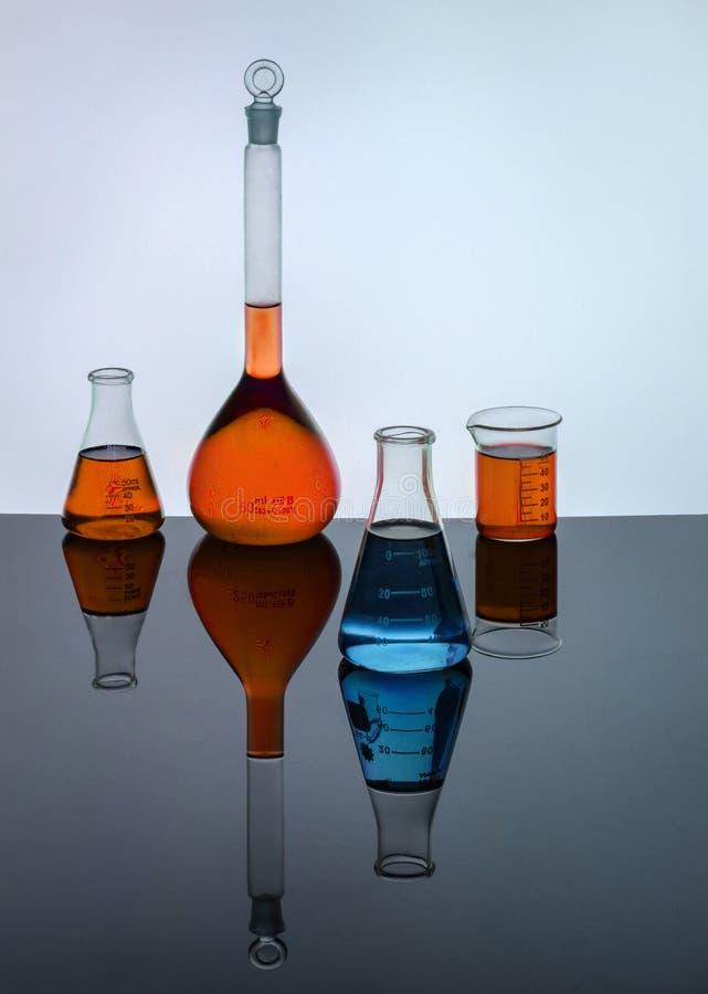 Εργαστηριακά γυαλικά που περιέχουν τις χρωματισμένες λύσεις στοκ φωτογραφίες με δικαίωμα ελεύθερης χρήσης