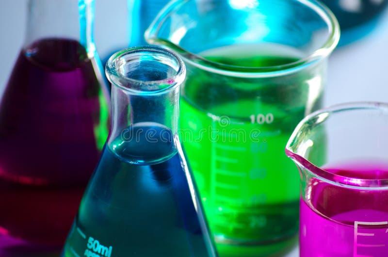 Εργαστηριακές κούπες χημείας περιέχουσες ρόδινες, μπλε και πράσινες λύσεις σε μια απεικονίζοντας επιφάνεια στοκ φωτογραφίες