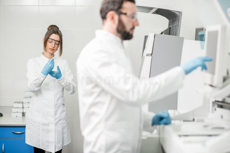 Εργαστηριακοί βοηθοί που εργάζονται με το analizer στοκ φωτογραφία