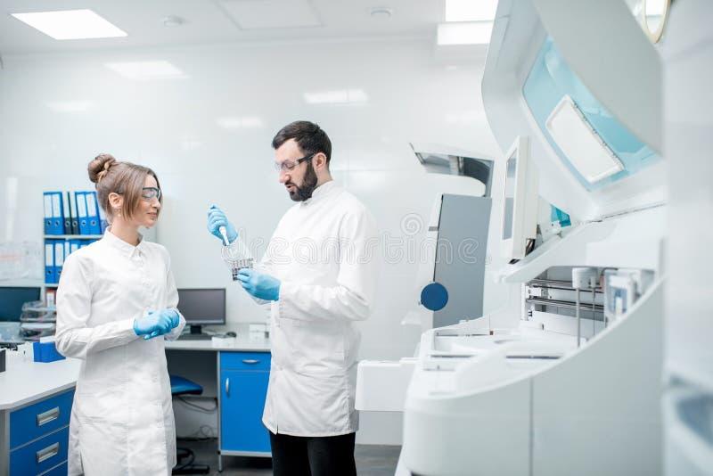 Εργαστηριακοί βοηθοί workign με τους σωλήνες δοκιμής στοκ εικόνες