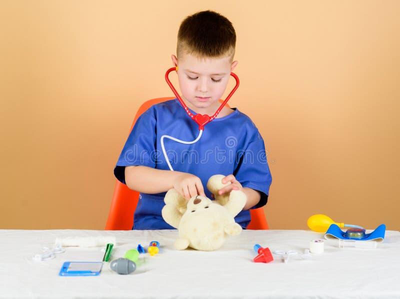εργαστηριακός βοηθός νοσοκόμων r γιατρός παιδιών με το στηθοσκόπιο Οικότροφος παιδιάτρων μικρό αγόρι σε ιατρικό στοκ φωτογραφία με δικαίωμα ελεύθερης χρήσης