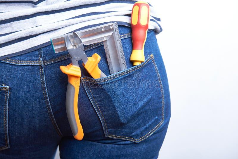 Εργαλεία για τον ηλεκτρολόγο στην πίσω τσέπη του τζιν παντελόνι που φοριέται από μια γυναίκα στοκ εικόνες