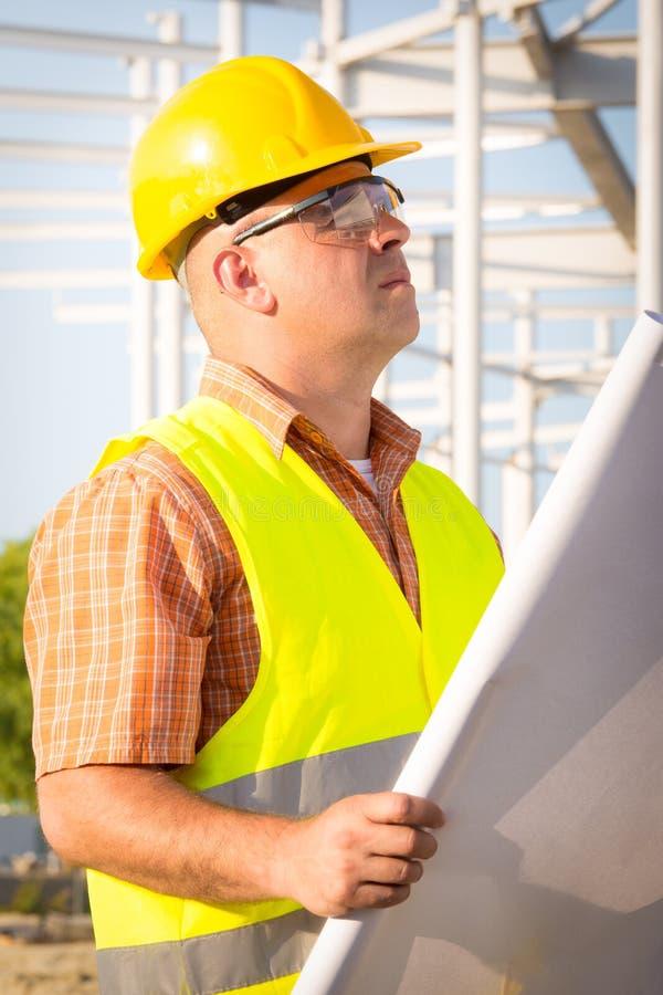 Εργοτάξιο ελέγχου διευθυντών κατασκευής με το σχέδιο στοκ εικόνες με δικαίωμα ελεύθερης χρήσης