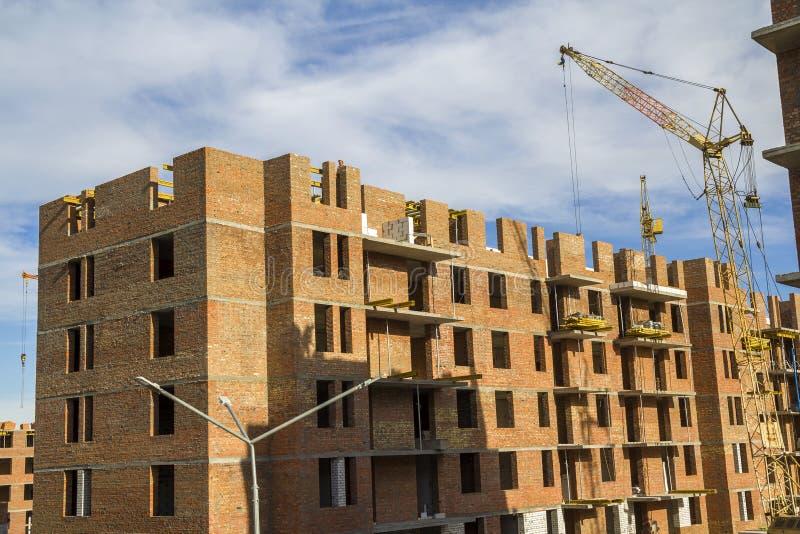 Εργοτάξιο οικοδομής ενός νέου υψηλού κτηρίου διαμερισμάτων με τους γερανούς πύργων ενάντια στο μπλε ουρανό Ανάπτυξη κατοικήσιμης  στοκ φωτογραφία με δικαίωμα ελεύθερης χρήσης