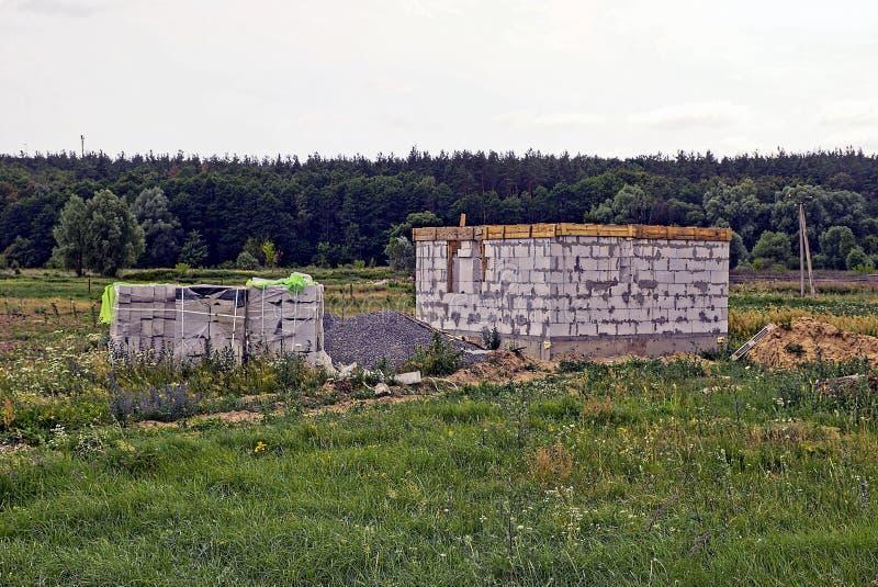 Εργοτάξιο οικοδομής με το ατελές σπίτι του άσπρου τούβλου στον τομέα στη χλόη στοκ φωτογραφία