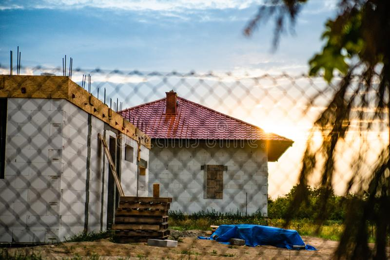 Εργοτάξιο οικοδομής Το ατελές σπίτι, που στηρίζεται στην επαρχία με το ηλιοβασίλεμα στο υπόβαθρο Να αναπτυχθεί σύγχρονου αστικού στοκ φωτογραφία