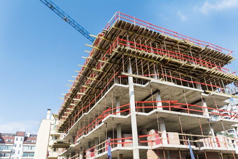 Εργοτάξιο οικοδομής με το κτήριο υλικών σκαλωσιάς και το γερανό πύργων στοκ φωτογραφίες