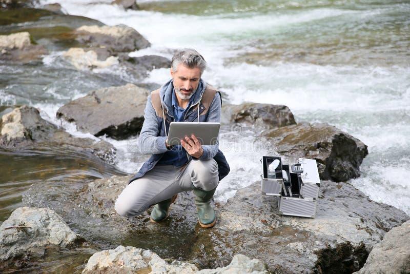 Ερευνητής βιολόγων που ελέγχει την ποιότητα νερού στοκ εικόνα