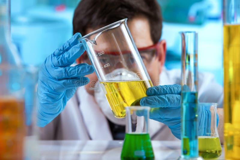 Ερευνητής που μετρά το δείγμα στην κούπα των υγρών στο ερευνητικό εργαστήριο στοκ εικόνα με δικαίωμα ελεύθερης χρήσης