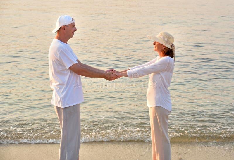 Ερωτευμένα χέρια εκμετάλλευσης ζεύγους στην αμμώδη παραλία στο ηλιοβασίλεμα στοκ φωτογραφίες