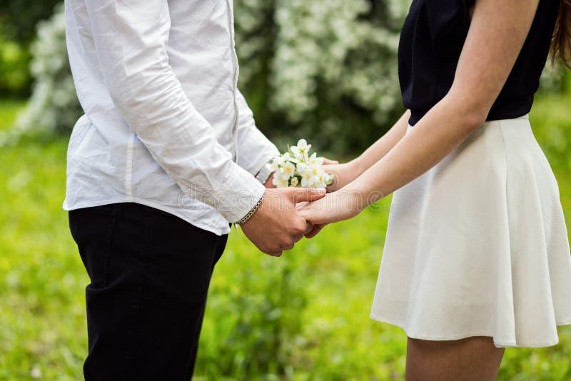 Ερωτευμένα χέρια ζεύγους σχετικά με το λουλούδι, λουλούδι στον κήπο bloss στοκ εικόνες με δικαίωμα ελεύθερης χρήσης