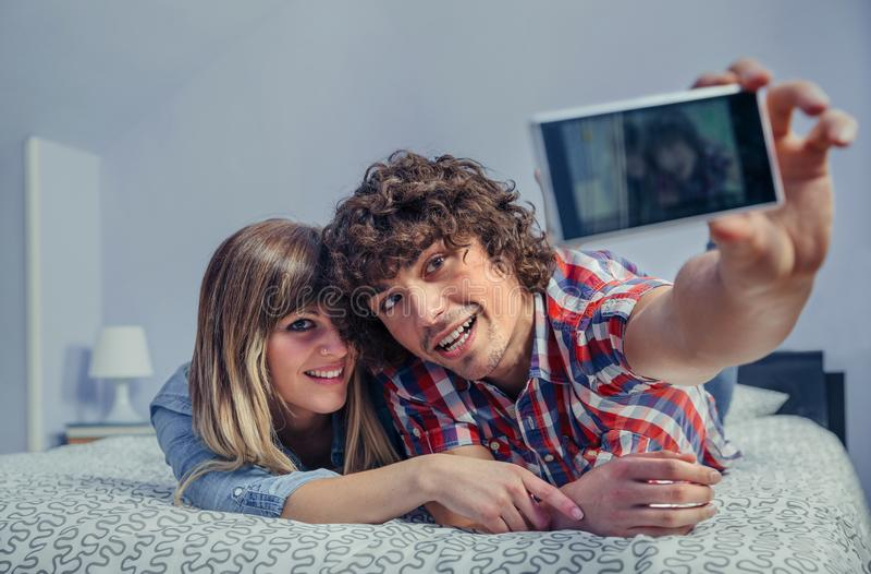 Ερωτευμένη λήψη ζεύγους selfie με το smartphone στο κρεβάτι στοκ εικόνες