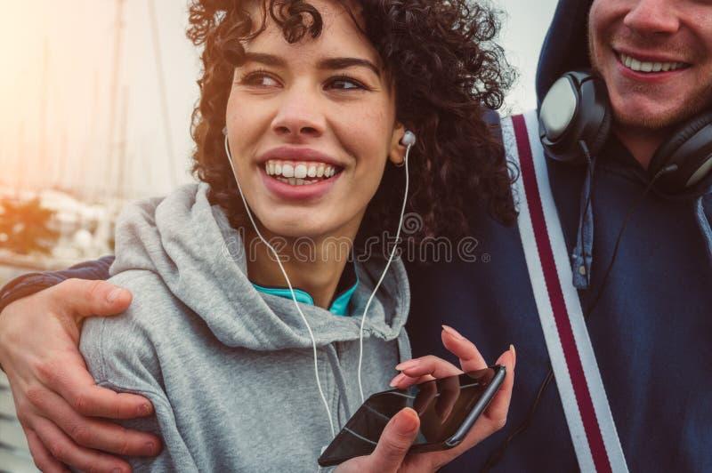 Ερωτευμένη μουσική ακούσματος ζεύγους από τα ακουστικά που χρησιμοποιούν το smartphone στοκ εικόνα