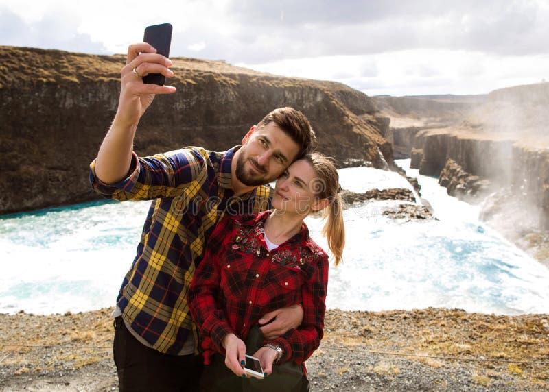 Ερωτευμένη παραγωγή Selfie ζεύγους σε έναν καταρράκτη στοκ εικόνα