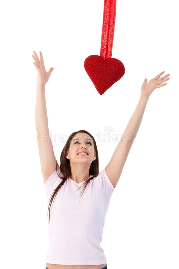 Ερωτευμένη προσπάθεια γυναικών να φθάσουν στο κόκκινο χαμόγελο καρδιών στοκ φωτογραφία με δικαίωμα ελεύθερης χρήσης