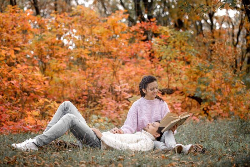 Ερωτευμένη συνεδρίαση ζεύγους στο πάρκο φθινοπώρου και το βιβλίο ανάγνωσης στοκ φωτογραφία με δικαίωμα ελεύθερης χρήσης