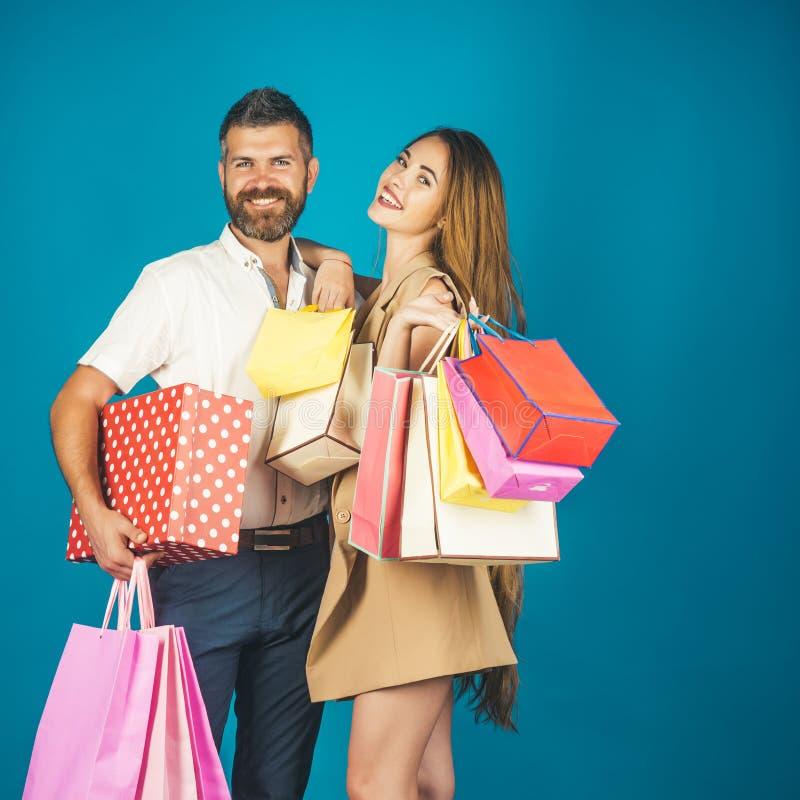 Ερωτευμένη τσάντα αγορών λαβής ζεύγους κοντά στον μπλε τοίχο στοκ εικόνα