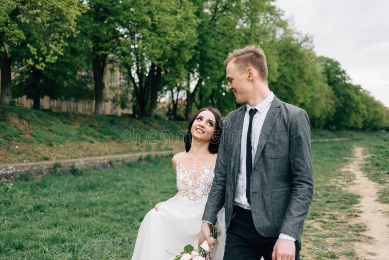 Ερωτευμένο περπάτημα ζεύγους στο πράσινο πάρκο στη ημέρα γάμου τους στοκ εικόνες