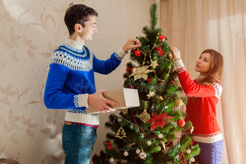 Ερωτευμένο χριστουγεννιάτικο δέντρο διακόσμησης ζεύγους στο σπίτι, που φορά τα χειμερινά πουλόβερ Να προετοιμαστεί στο νέο έτος στοκ φωτογραφίες με δικαίωμα ελεύθερης χρήσης