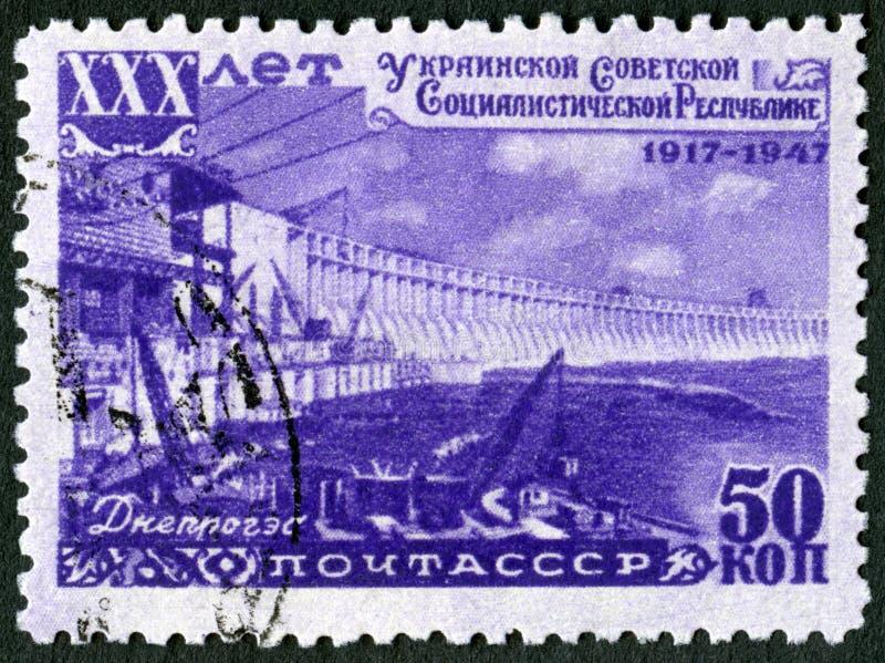 ΕΣΣΔ - 1947: παρουσιάζει φράγμα Dnieprostroy, υδροηλεκτρικός σταθμός Dnieper, σειρά ουκρανικό SSR, 30η επέτειος στοκ εικόνα με δικαίωμα ελεύθερης χρήσης