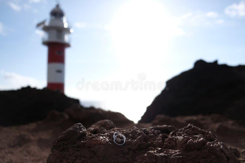 Εστίαση στα γαμήλια δαχτυλίδια στον ηφαιστειακό βράχο με το θολωμένο κόκκινο και άσπρο φάρο στο υπόβαθρο στοκ εικόνες