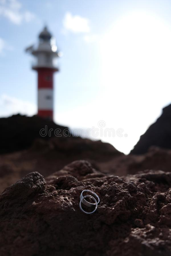 Εστίαση στα γαμήλια δαχτυλίδια στον ηφαιστειακό βράχο με το θολωμένο κόκκινο και άσπρο φάρο στο υπόβαθρο στοκ φωτογραφία