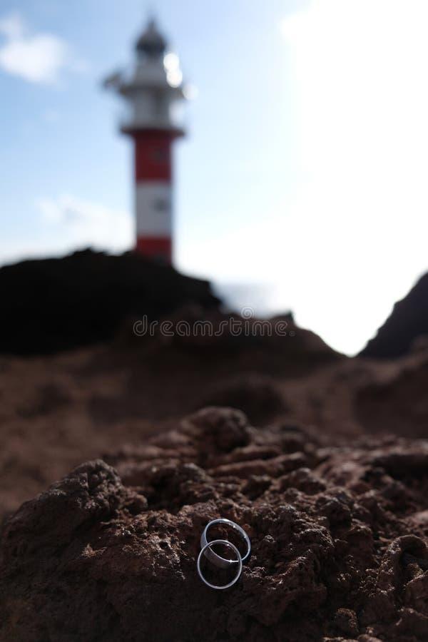 Εστίαση στα γαμήλια δαχτυλίδια στον ηφαιστειακό βράχο με το θολωμένο κόκκινο και άσπρο φάρο στο υπόβαθρο στοκ φωτογραφία με δικαίωμα ελεύθερης χρήσης