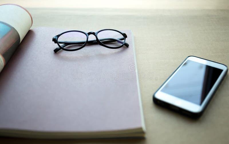 Εστίαση στα γυαλιά με το τηλέφωνο και το βιβλίο κυττάρων στοκ εικόνα με δικαίωμα ελεύθερης χρήσης