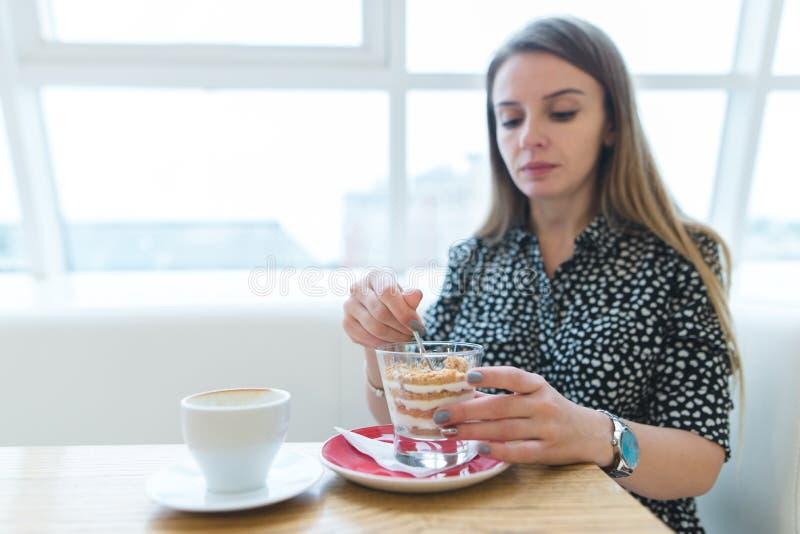 Εστίαση στο επιδόρπιο Μια όμορφη γυναίκα τρώει ένα ορεκτικό, όμορφο επιδόρπιο σε έναν σύγχρονο και ελαφρύ καφέ στοκ εικόνες